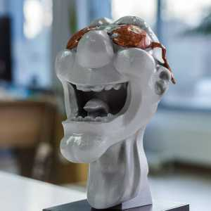3D print of head painted grey with brown accents and a stone base
